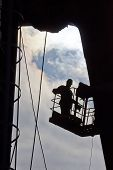 image of millwright  - Silhouette of builder working at height - JPG