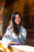 stock photo of national costume  - Young woman in ukrainian national costume at the wooden sun-parlour