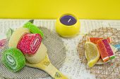 stock photo of decoupage  - Colorful jelly rolls on a handmade decoupage wooden spoon - JPG