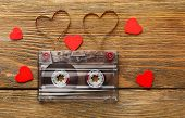 stock photo of heart sounds  - Audio cassette with magnetic tape in shape of hearts on wooden background - JPG