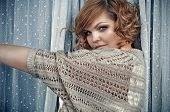 pic of cold-shoulder  - Mysterious trendy woman with short curly hair wearing a beige cardigan is standing by the window between white long dotty lace curtains and looking over her left shoulder - JPG