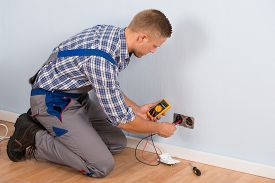 pic of ohm  - Male Electrician Checking Voltage Of Socket With Multimeter In House - JPG
