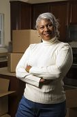 Portrait of middle-aged African-American female in kitchen with moving boxes.