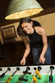 Young woman smiling while playing foosball game at pub.