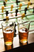 Two glasses of beer on foosball table.