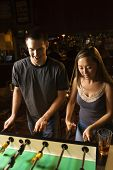 Young couple teamed up at foosball game in pub.