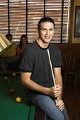 Portrait of young man leaning on billiards table holding pool stick.