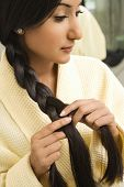 Close up profile of Asian/Indian young woman braiding hair.