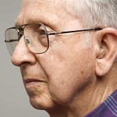 Close-up profile portrait of Caucasian elderly man with glasses and hearing aid.