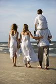 Caucasian family of four walking on beach with dad carrying son on shoulders.