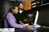 African-American and Indian young adult business women looking and pointing at computer in office.