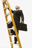 Caucasian middle-aged businessman climbing ladder carrying briefcase.
