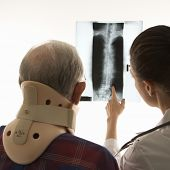 Over the shoulders view of mid-adult Caucasian female pointing at an x-ray as elderly Caucasian male