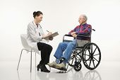 Mid-adult Caucasian female doctor taking notes with an elderly Caucasian male in wheelchair to her s