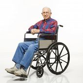 Portrait of Caucasion elderly man sitting in wheelchair smiling at viewer.