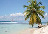 stock photo of sail-boats  - a sailboat sailing past a deserted island in the caribbean - JPG