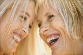 Portrait of Caucasian mother and daughter laughing and looking at each other.