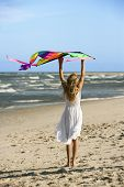 Caucasian pre-teen girl holding kite on beach.