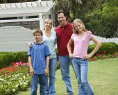 Caucasian family of four posing for portrait in yard.