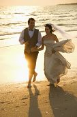 Caucasian mid-adult bride and mid-adult groom holding hands running barefoot on beach.