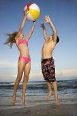 Caucasiana pré-adolescente menina e menino brincando com beachball na praia.