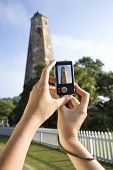 Close up of Caucasian woman's hands holding digital camera and photographing lighthouse at Bald Head