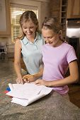 Caucasian mid-adult mother helping pre-teen daughter with homework at kitchen counter.