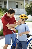Caucasian mid-adult dad strapping bicycle helmet on pre-teen son.