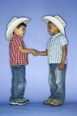 Hispanics und Afroamerikanern männliches Kind in Cowboy-Hüte, die Hände schütteln.