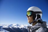 Caucasian teenage boy snowboarder wearing helmet and goggles on mountain in Whistler, British Columb