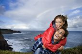 Caucasian mid-adult couple piggybacking by ocean with rainbow in background in Maui, Hawaii.