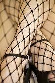 Close up of Caucasian woman in fishnet stockings and high heels.