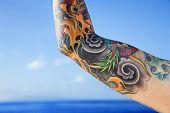 Close-up van de arm getatoeëerd vrouw met grote oceaan op achtergrond in Maui, Hawaii, Verenigde Staten.