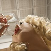 Low angle view of attractive Caucasian woman drinking a martini.