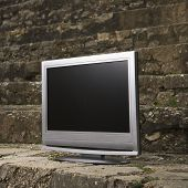 Flat panel television set in front of gray brick wall.