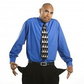 African American man in suit pulling out empty pockets and shrugging.