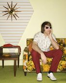 Caucasian mid-adult man wearing sunglasses sitting on colorful retro sofa looking bored.