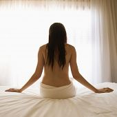 Back view portrait of pretty Caucasian young woman partially nude sitting on bed by sunlit window.