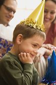 Caucasian boy at  birthday party looking to the side and smiling.