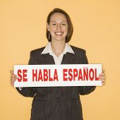 Caucasian businesswoman smiling holding sign reading