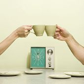 Caucasian male and female hands toasting with coffee cups across retro kitchen table setting.