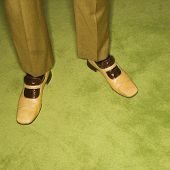Close-up of Caucasian mid-adult male feet in vintage shoes against green rug.