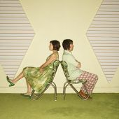Caucasian mid-adult couple wearing vintage clothing sitting back to back in green vinyl chairs with