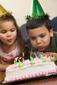 Hispanic girl and boy wearing party hats blowing out candles on birthday cake.