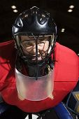 Woman hockey goalie wearing helmet sneering looking intimidating.