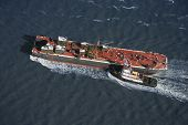 Aerial view of tugboat pushing tanker.