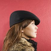 Profile of young brunette adult Caucasian woman wearing flat hat.