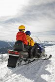 Man and woman riding on snowmobile in snowy mountainous terrain.
