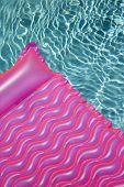Pink float in empty swimming pool with rippling blue pool.