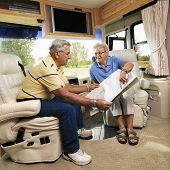Senior couple sitting in RV looking at map and smiling.